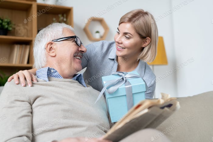 Happy young blonde female giving her mature father blue giftbox with present