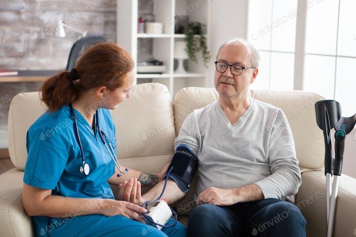 Старший мужчина в доме престарелых с цифровым устройством артериального давления