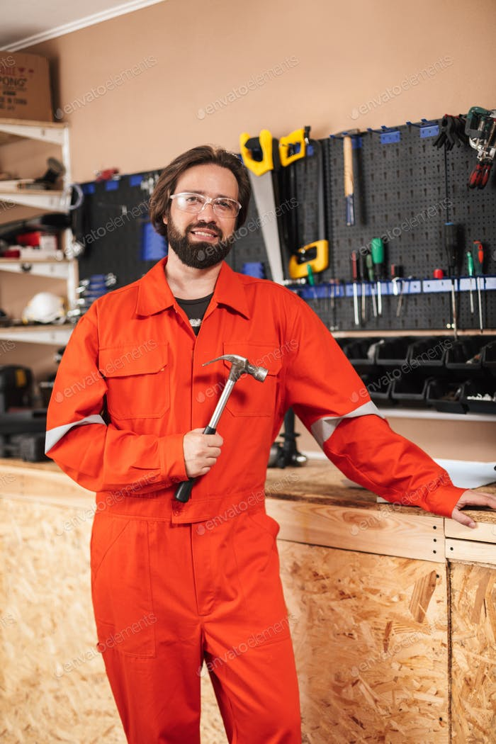 Smiling foreman in orange work clothes and protective eyewear ho