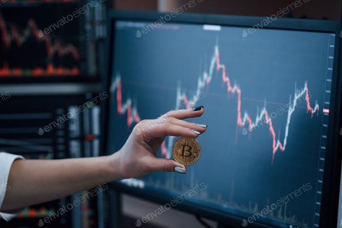 Front view. Woman's hand holding bitcoin in modern office with many monitors with graphs