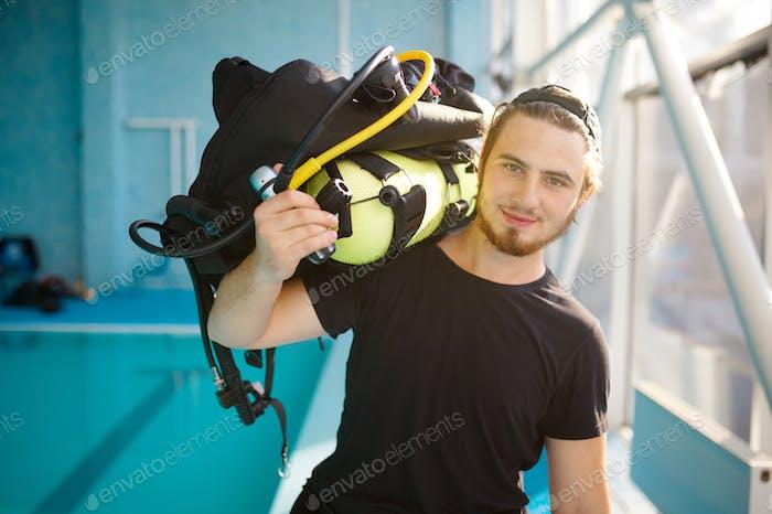 Male diver holds scuba gear, diving school
