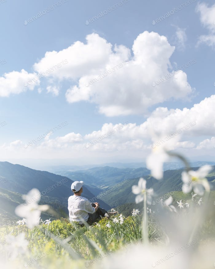 A tourist in white clothes sits in a mountain meadow