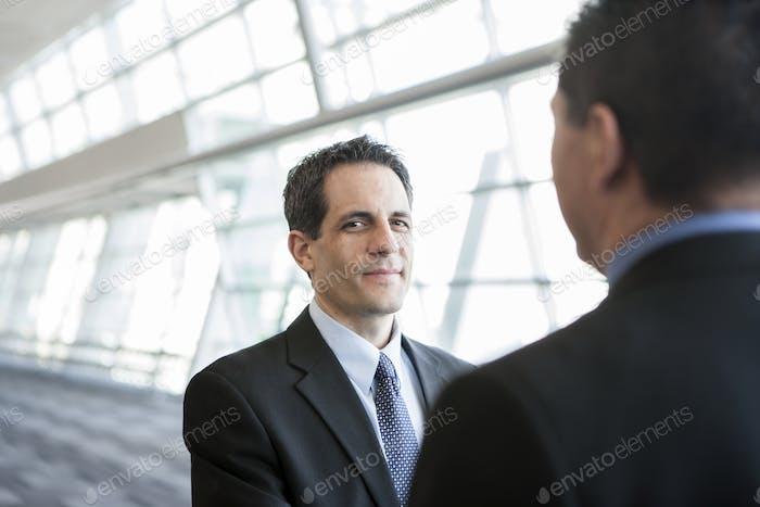 Бизнесмен смотрит на камеру во время обсуждения в лобби конференц-центра.