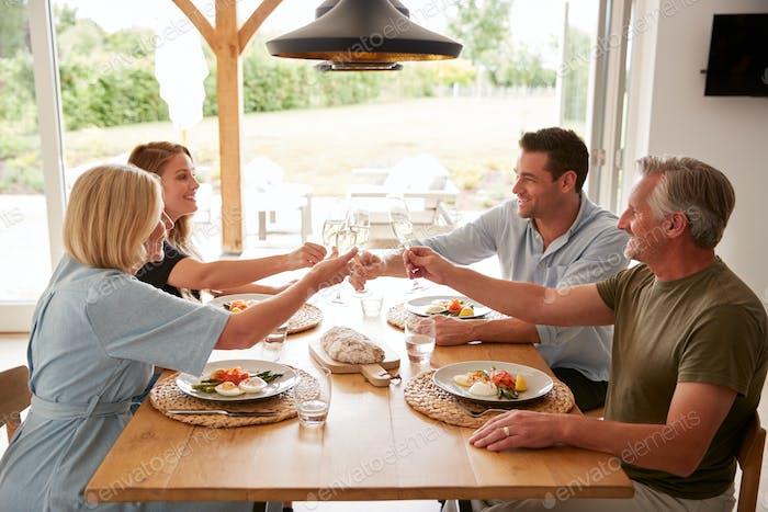 Family With Senior Parents And Adult Offspring Make A Toast Before Eating Meal Around Table At Home