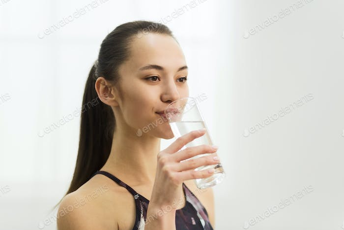 Millennial woman drinking clean fresh water after training