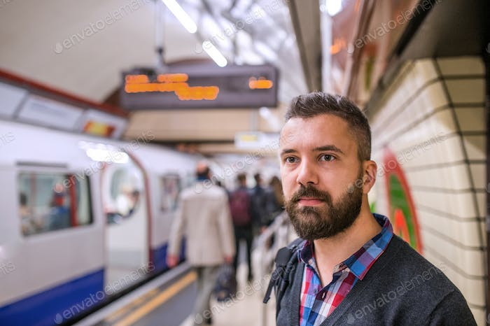 Young hipster man standing at the underground platform waiting
