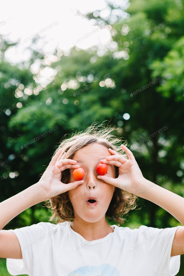 Cheerful girl playing with plums