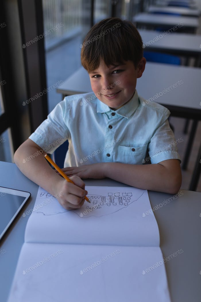 Schoolboy drawing on notebook and looking at camera at desk in classroom of elementary school
