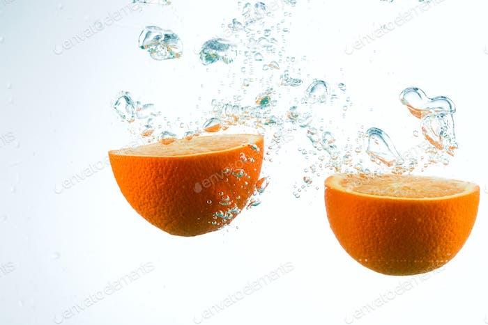 Orange in Wasserströmen auf weißem Hintergrund
