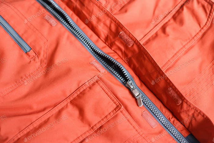 Part of a zipper with a lock on red cloth