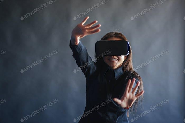 Glückliche Frau auf schwarzem Hintergrund im Studio bekommt die Erfahrung der Verwendung von VR-Brillen