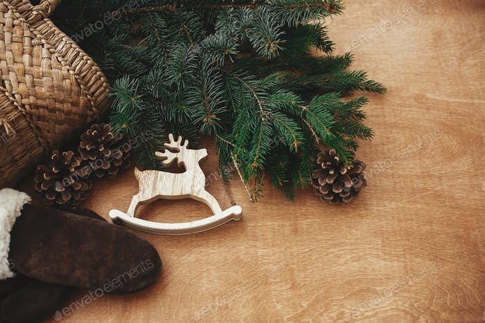 Rustic reindeer toy, gloves, basket with fir branches and cones on rustic wooden background