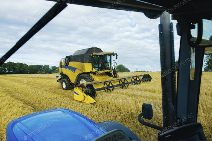 A combine harvester working alongside a tractor on a crop in a field.