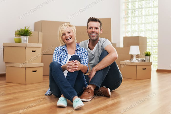 Portrait of laughing couple in new home