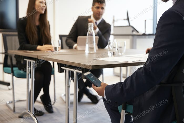 Businessman Discreetly Replying To Text Message During Meeting