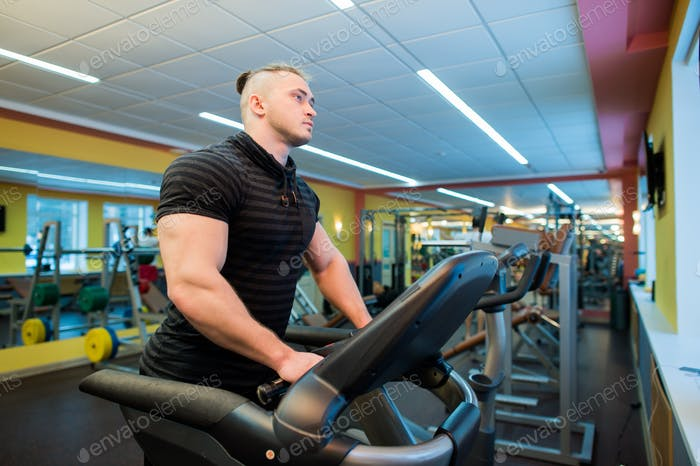 Attractive young muscular man while running on a treadmill in gym