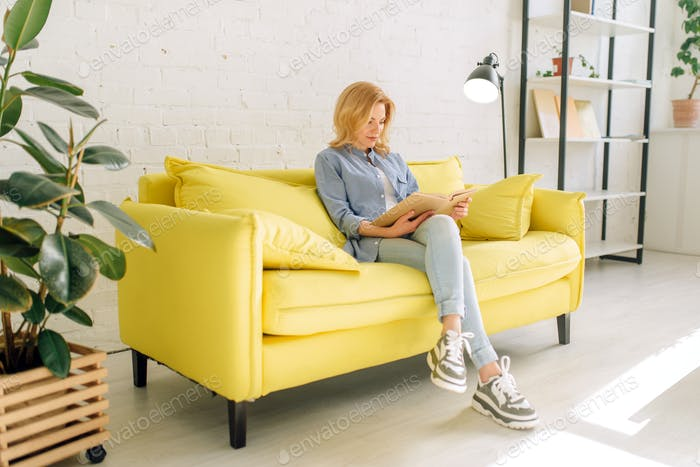 Young woman reading a book on cozy yellow couch