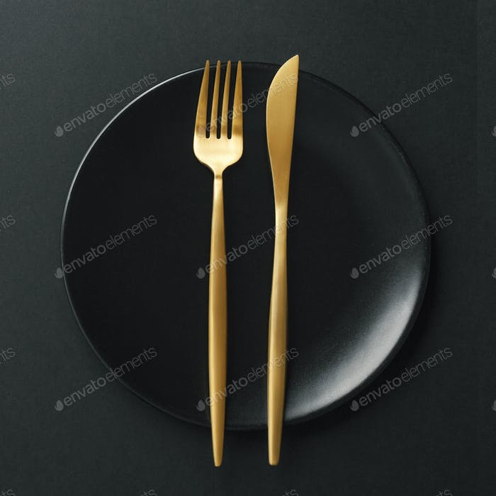Gold cutlery set on black background
