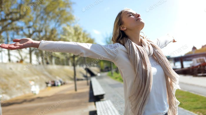 Pretty young woman enjoying the spring with arms raised to the s