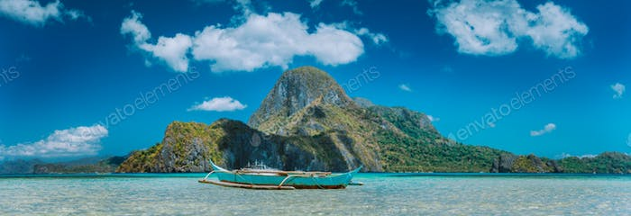 El Nido, fishermen's boat in blue bay with panoramic view of Cadlao Island in background