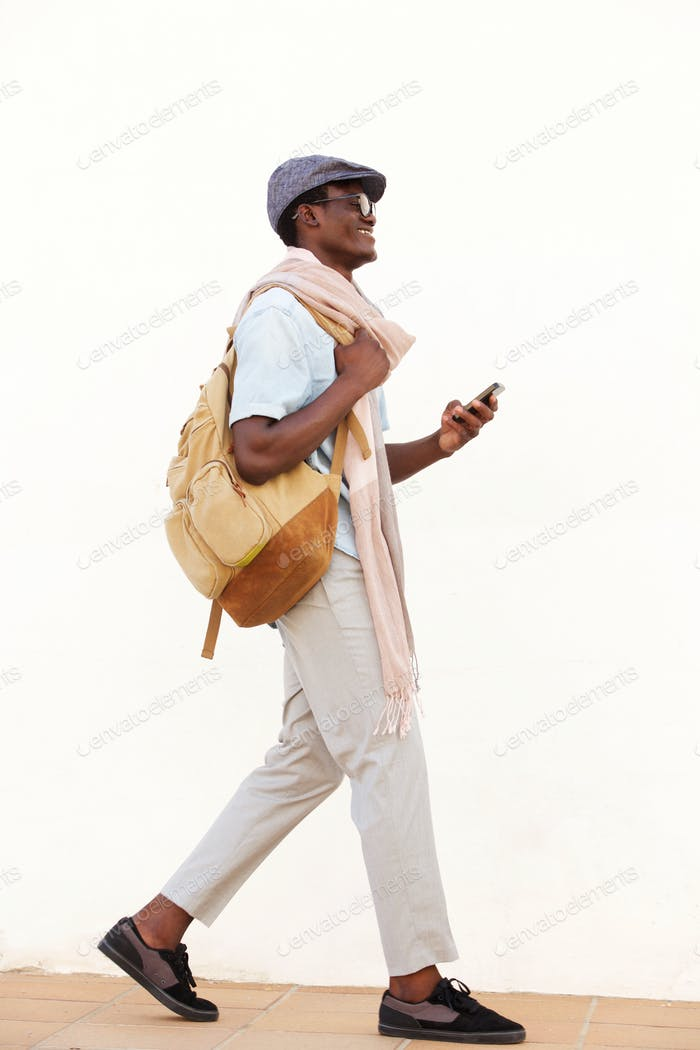 Side portrait of smiling African American man walking with cell phone