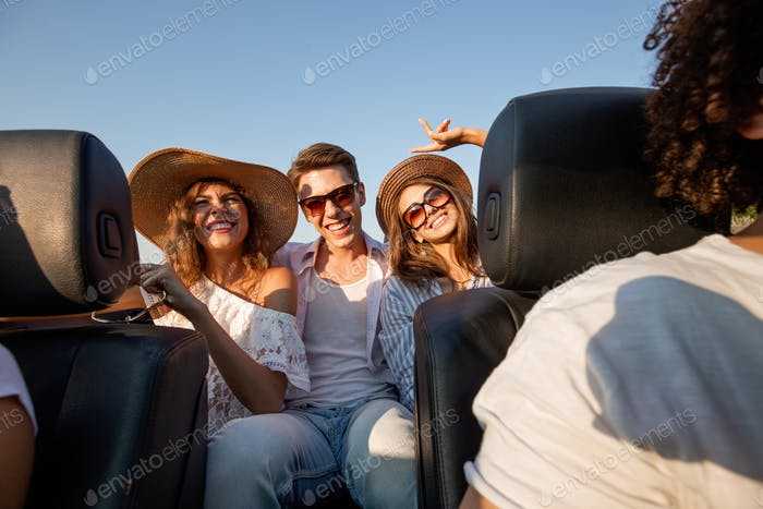 Charming young dark-haired women in hats are sitting with young man in a black cabriolet and smiling