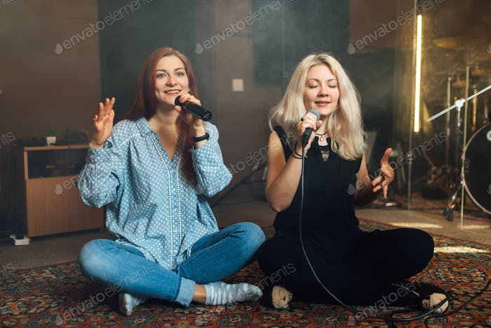 Two girlfriends sing in karaoke while sitting on the floor