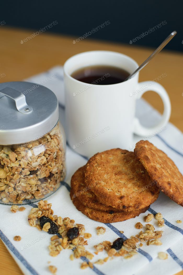 wholemeal oatmeal cookies stack with granola and tea on napkin
