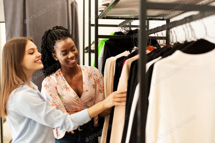 Fashion Stylist Helping Client Buy New Clothes In Clothing Store