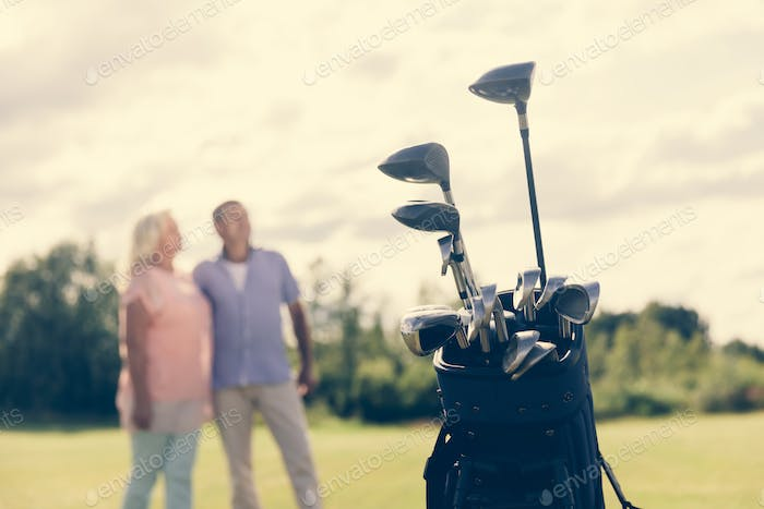 Golf bag standing on a grass field, people in the background