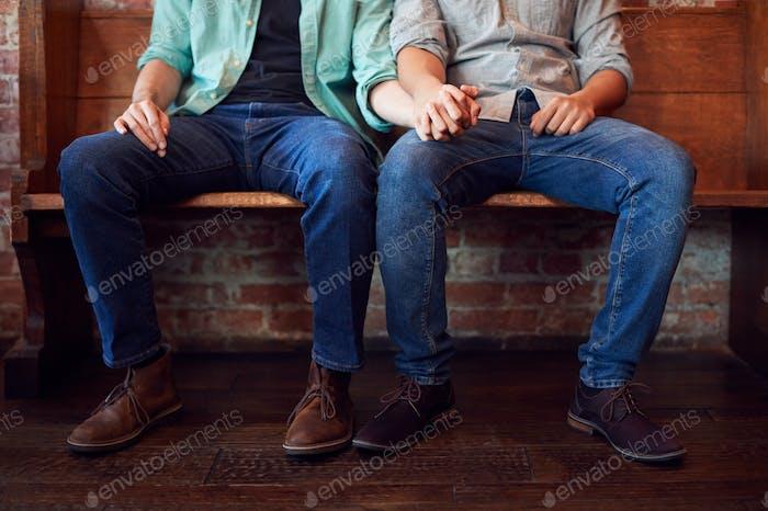 Nahaufnahme auf Füße des gleichen Geschlechts männliche paar halten Hände sitzen auf Bank zusammen