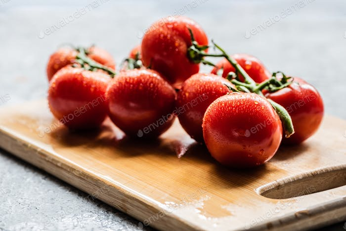 fresh ripe red tomatoes on branch with water drops on wooden board on grey concrete surface
