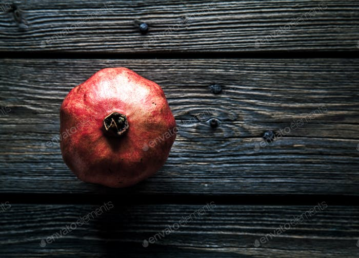 pomegranate on a wooden rustic background. fruit, food, look for useful