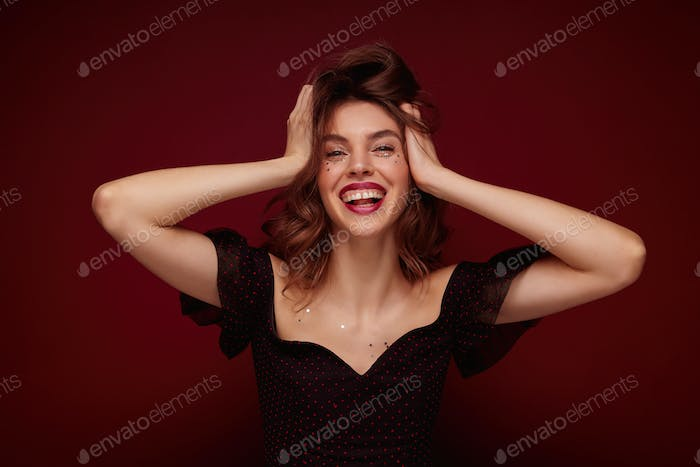 Indoor shot of young charming brunette lady in elegant black top with red dots clutching happily