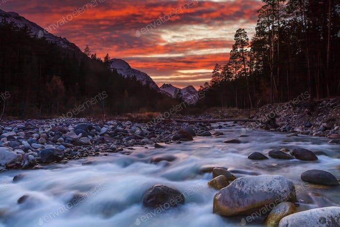 Hermosa puesta de sol sobre el río de montaña en verano