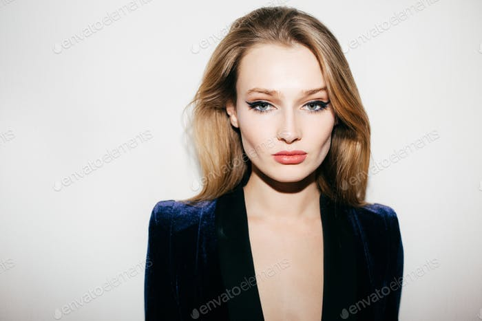 Beautiful lady in blue velvet jacket standing and thoughtfully looking in camera on white background