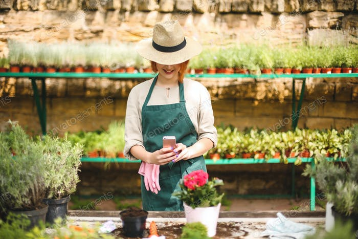 Young smiling lady in apron and hat standing and taking photos of flower in pot on her cellphone