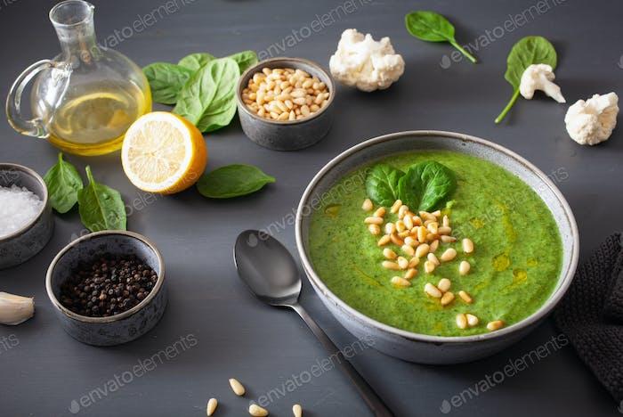 green creamy cauliflower spinach soup on gray background