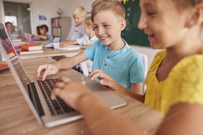 Two kids using laptop during lesson