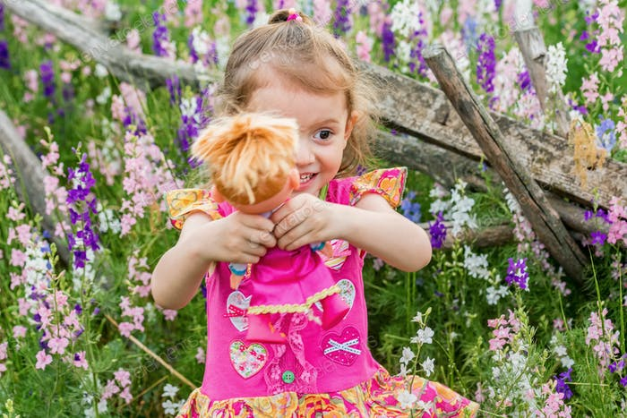 Cute baby girl in bright dress plays with doll outdoors in green field