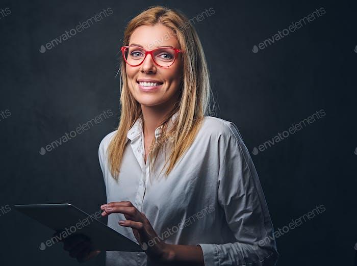 Ein blondes weibliches hält Tablet-PC auf grauem Hintergrund.