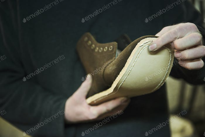Close up of worker in a shoemaker's workshop, attaching a sole to a leather boot.