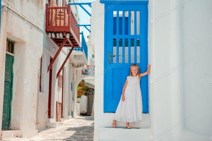 Entzückendes kleines Mädchen in der alten Straße des typischen griechischen traditionellen Dorfes