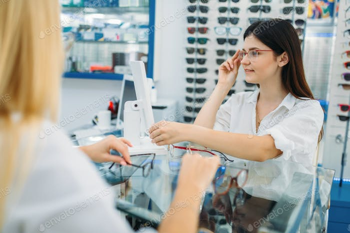 Female optician and consumer chooses glasses frame