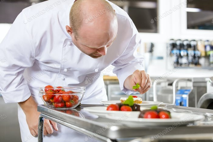 Chef decorates dessert cake with strawberry in kitchen