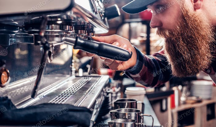 A man is making coffee in a professional coffee machine.