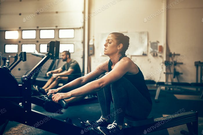 Two fit people exercising on rowing machines at the gym