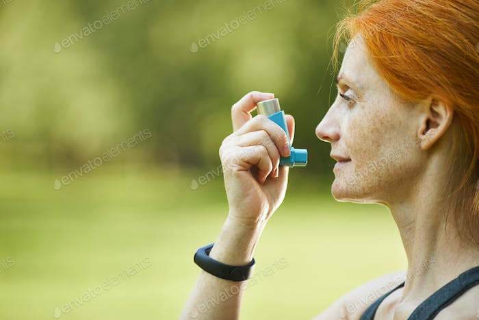 Redhead woman using inhaler outside