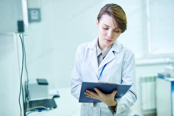 Doctor standing with clipboard and taking notes