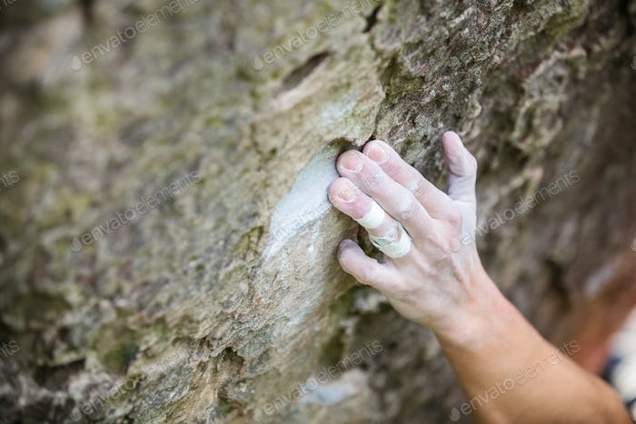 Rock climber's hand gripping small hold on natural cliff